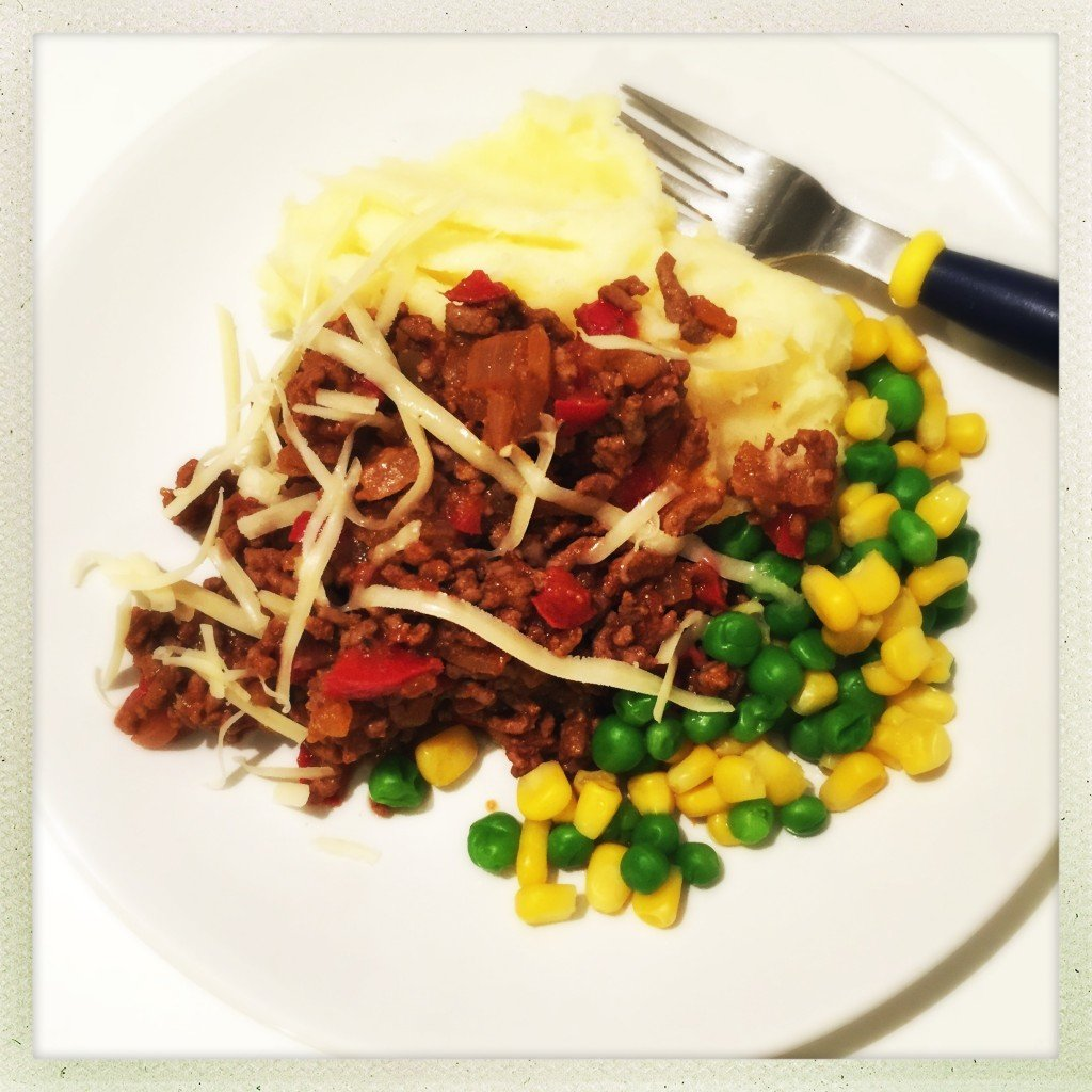 white plate with savoury minced beef and peppers spooned over cheesy mashed potatoes with peas and corn on the side