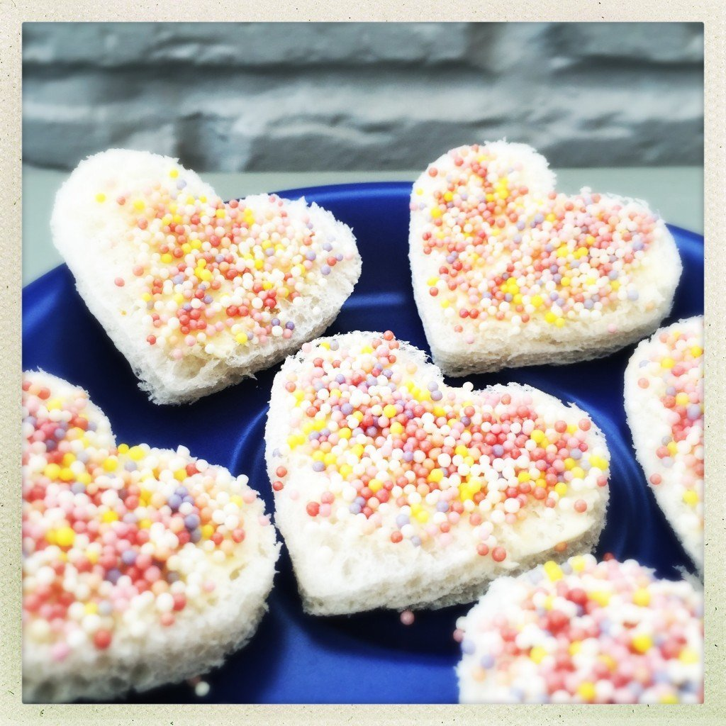 fairy bread cut into love heart shapes and covered in pastel hundreds and thousands sprinkles
