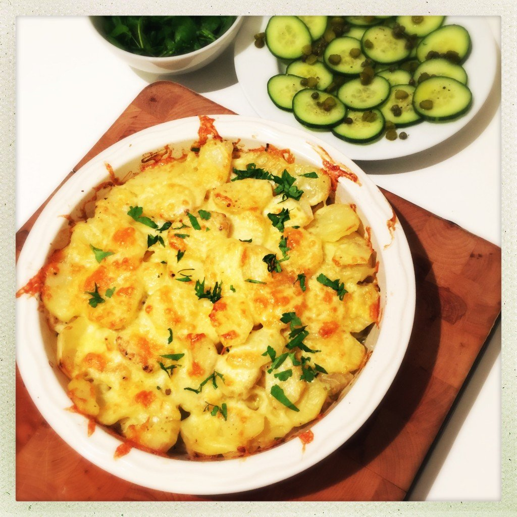 homemade cheesy vegetable hotpot with cheese and fresh herbs scattered over the top of the scalloped potatoes. Served alongside a platter of cucumber salad