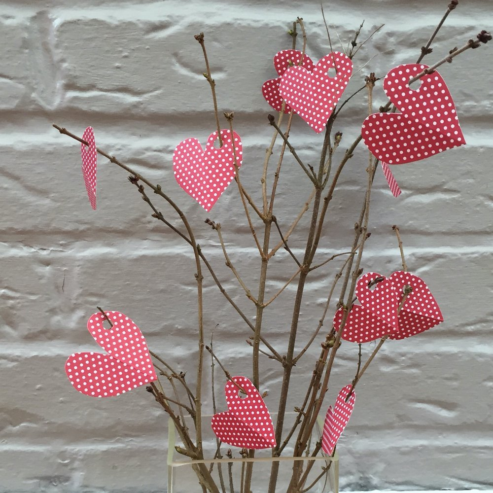 bare twigs in a glass vase with little paper hearts hanging from the twigs with little gratitude messages written on the back the hearts