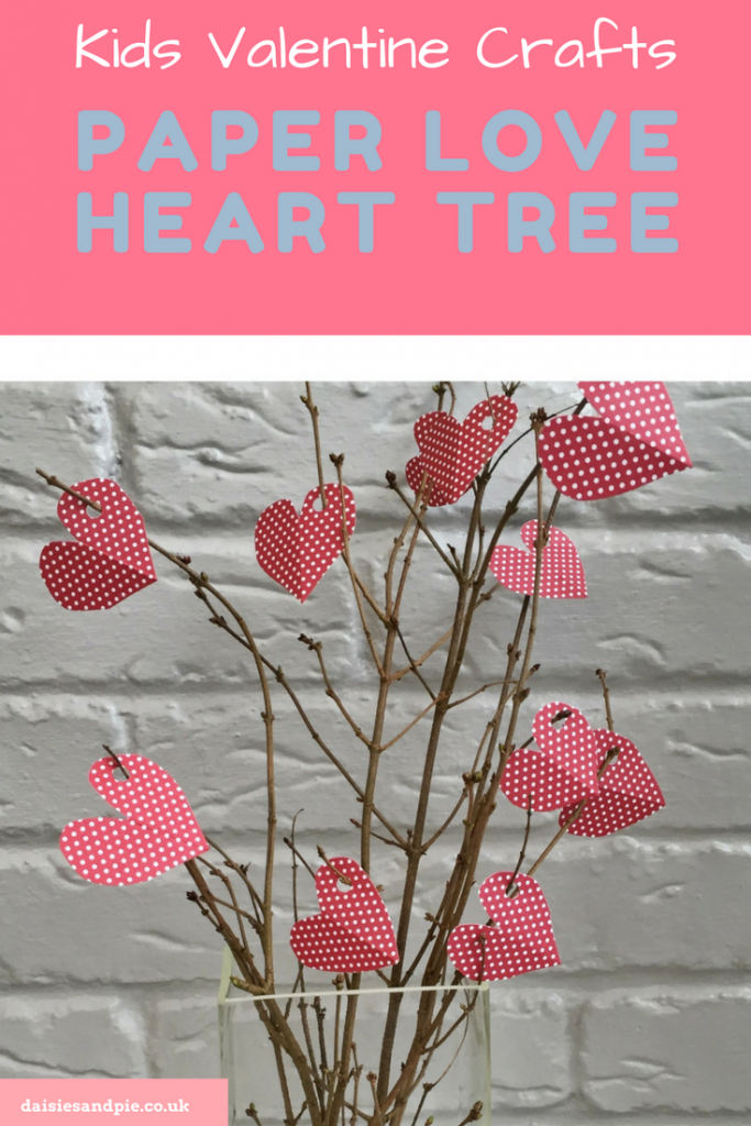 "glass vase with twigs arranged in it - little spotty red paper hearts with hole punch holes - hanging from the twigs set against a painted grey brick wall. Text overlay saying ""Kids Valentines Day Craft - Paper Love Heart Tree"""