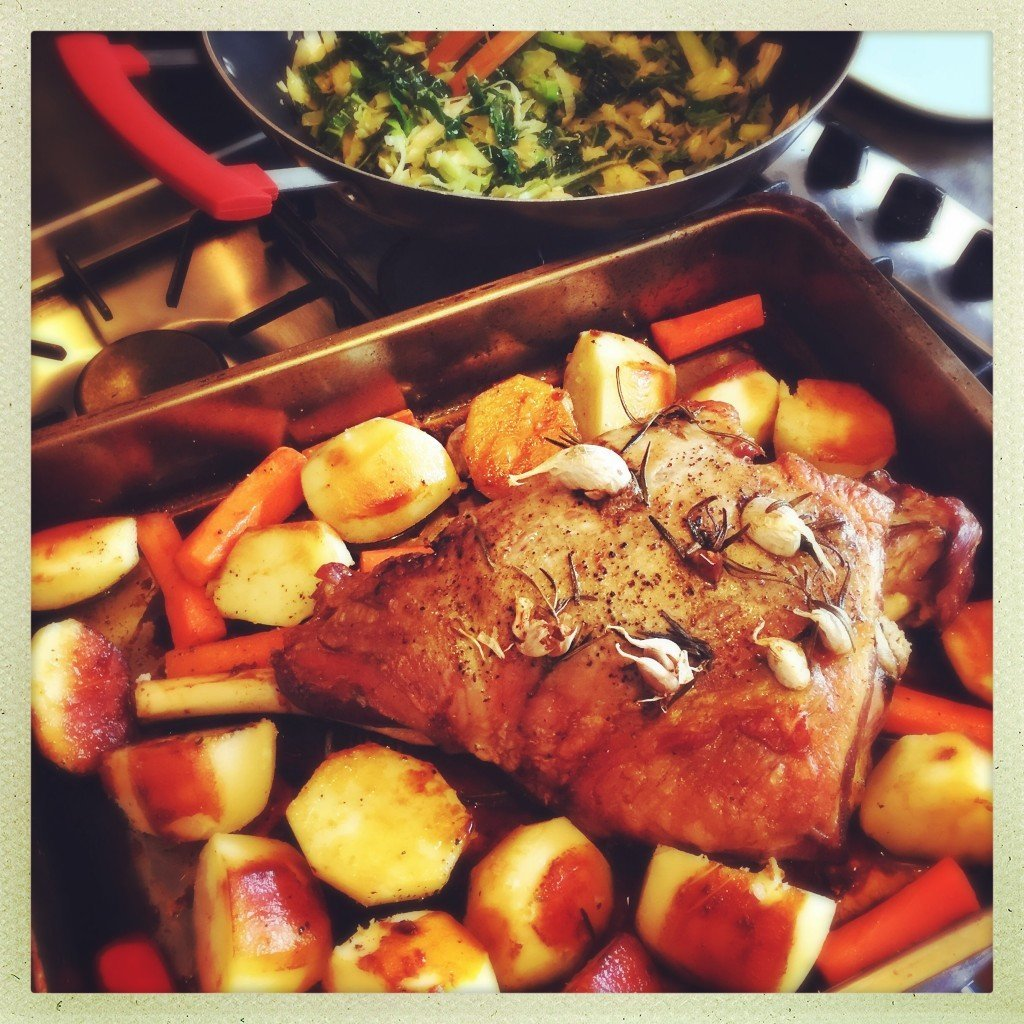 "roasting tin filled with roast potatoes and carrots with large leg of rosemary and garlic studded roast lamb. Text overlay saying "" super easy slow roasted lamb"""