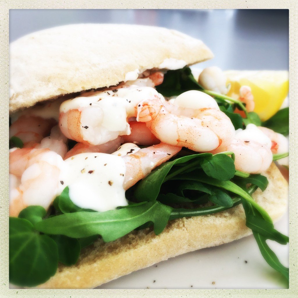 ciabatta roll stuffed with baby leaf salad, king prawns and lemon pepper yogurt dressing