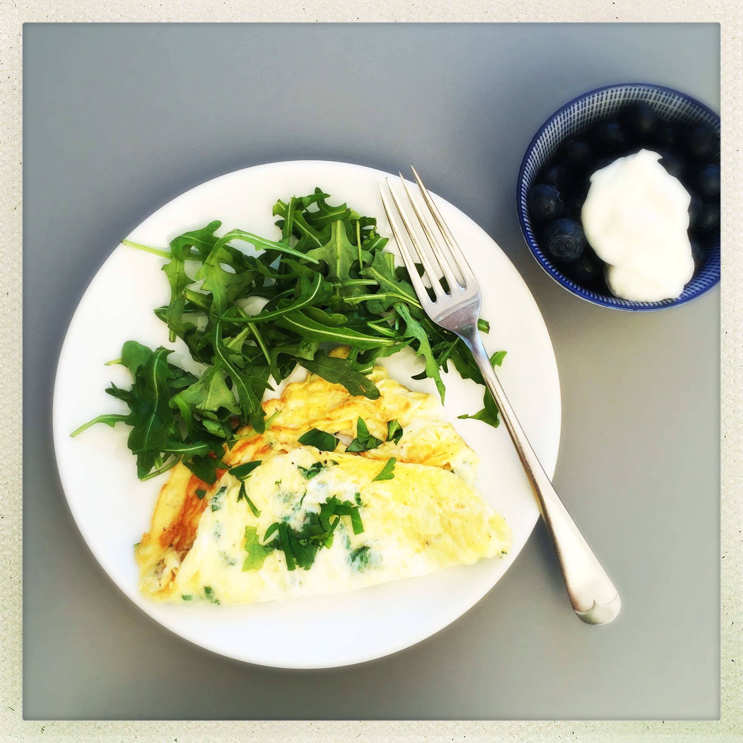 herby omelette with green salad - blueberries and yogurt in a bowl alongside
