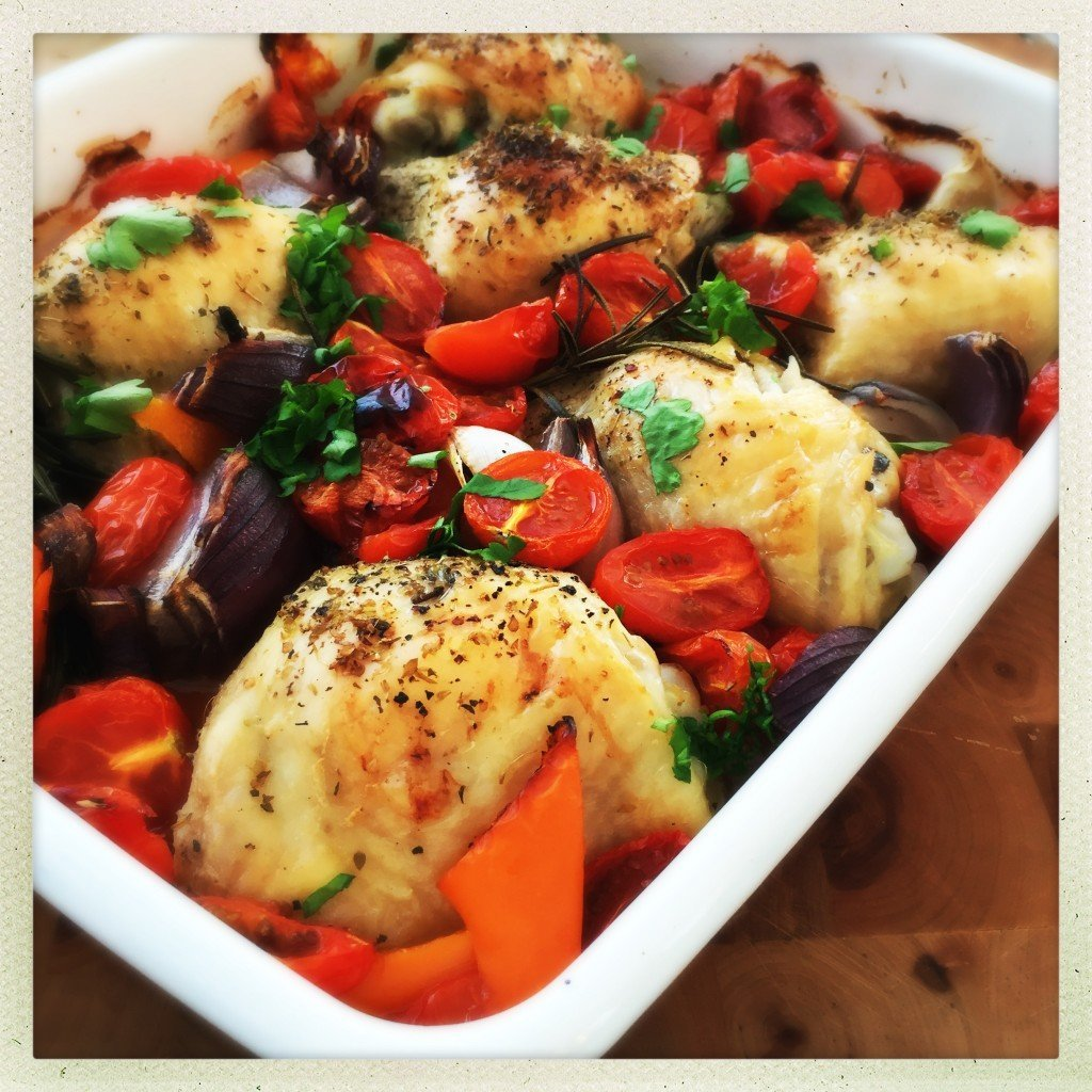 italian baked chicken thighs - wooden board with an enamel roasting tin filled with chicken traybake - chicken things, peppers, tomatoes, onions and herbs