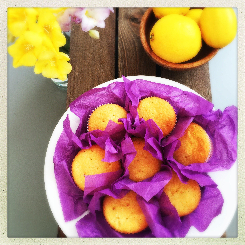 platter of lemon drizzle cupcakes wrapped in purple tissue alongside a bowl of lemons.