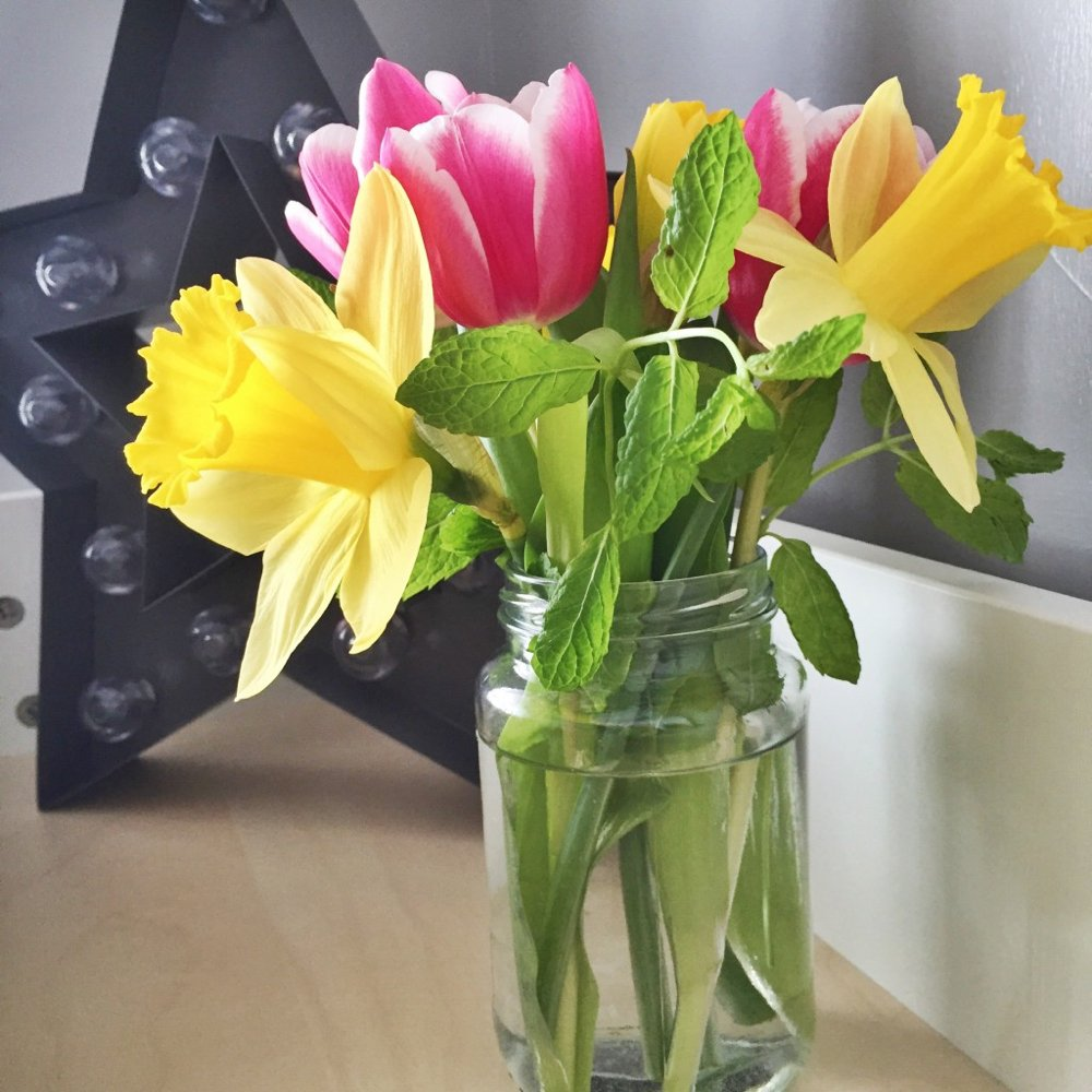 daffodils and pink tulips in a jam jar stood by a star light