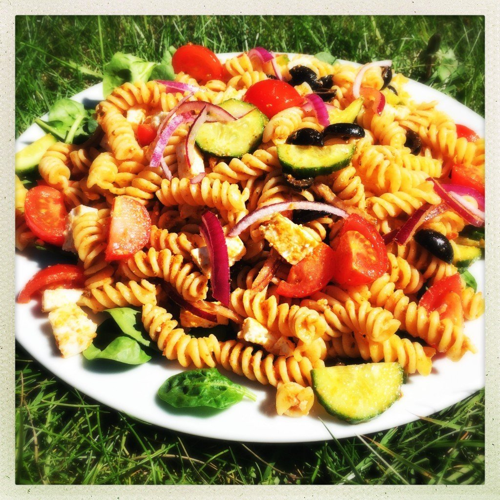 white plate piled high with greek pasta salad