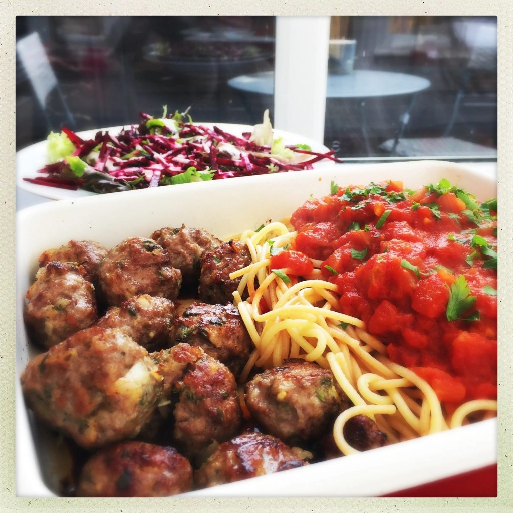 lamb meatballs with spaghetti and tomato sauce in an enamel roasting tin. Served alongside a beetroot salad