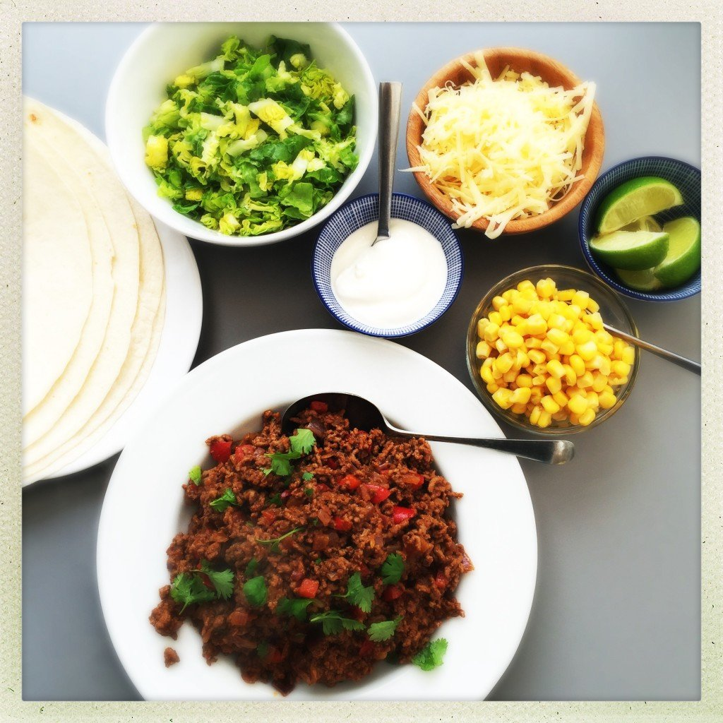 smoky beef burrito bar - dishes with smoky beef, sweetcorn, shredded lettuce, grated cheese, limes, and sour cream with plate or tortilla wraps