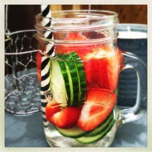 glass of infused water with strawberries and cucumbers stood on grey table