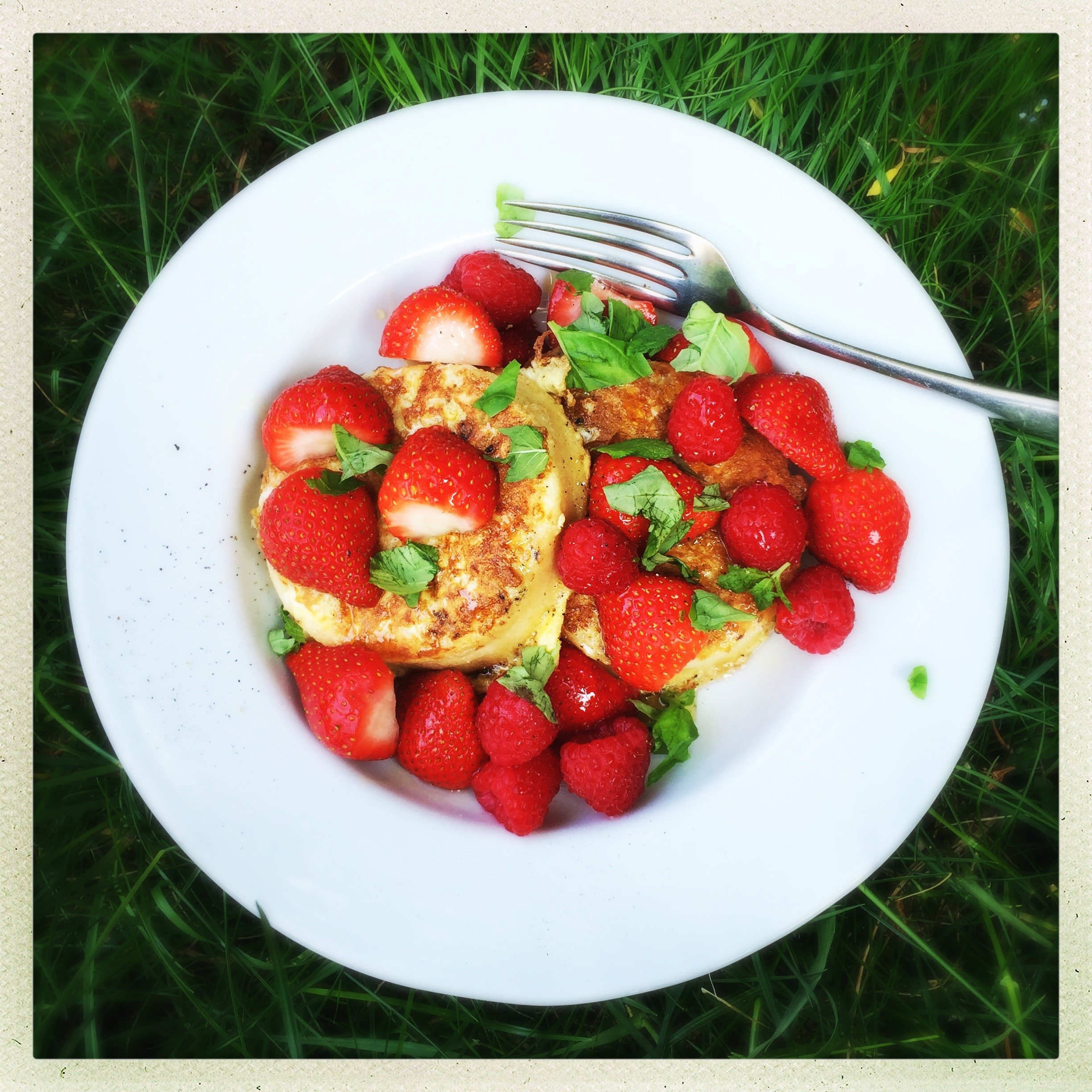white plate on the grass - plate loaded with eggy bread crumpets topped with strawberries, raspberries and scattered with fresh mint