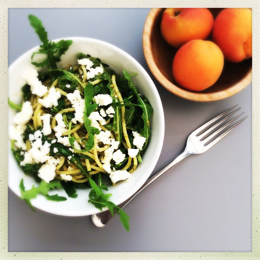 white bowlful of spaghetti tossed with pesto and rocket with feta cheese crumbled on top