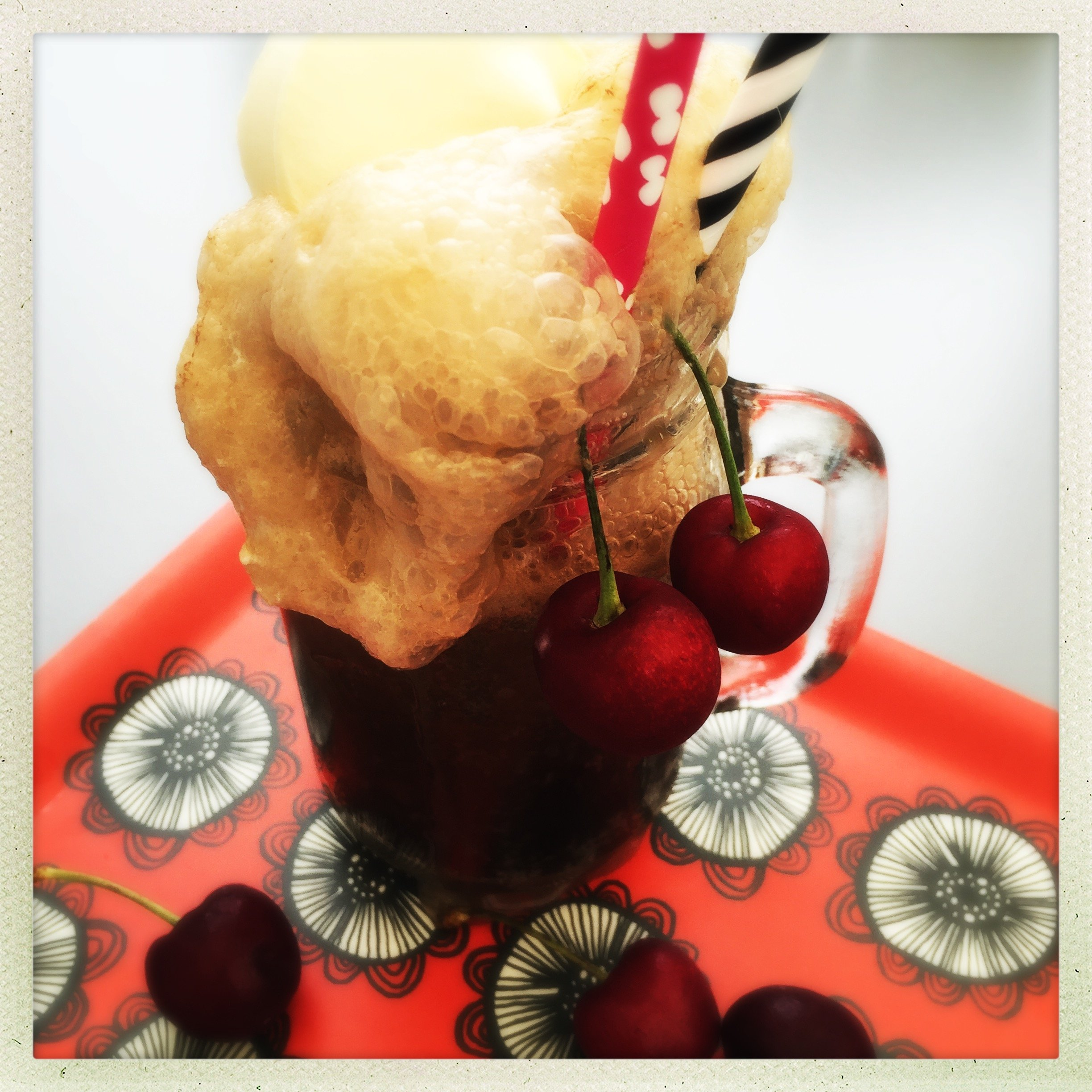 cherry coke float in a kilner jar mug with red and white spotty paper straw, black and white striped paper straw, cherries hanging from the glass - stood on red and white wooden tray