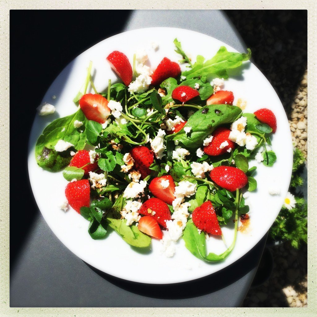 platter of strawberry and feta salad tossed with spinach, rocket and herbs and dressed in simple balsamic salad dressing