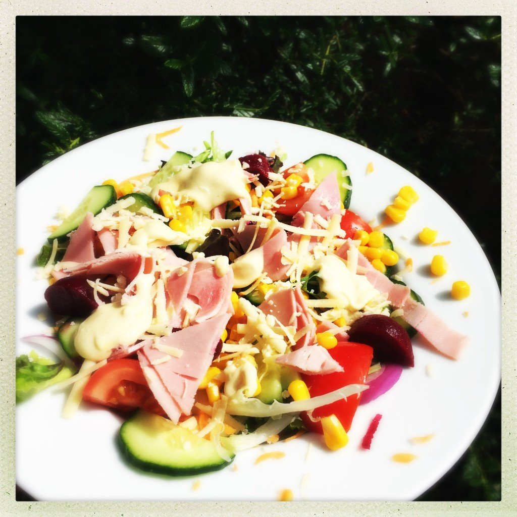 plate of ham salad with cheese and sweetcorn and drizzle of mayonnaise