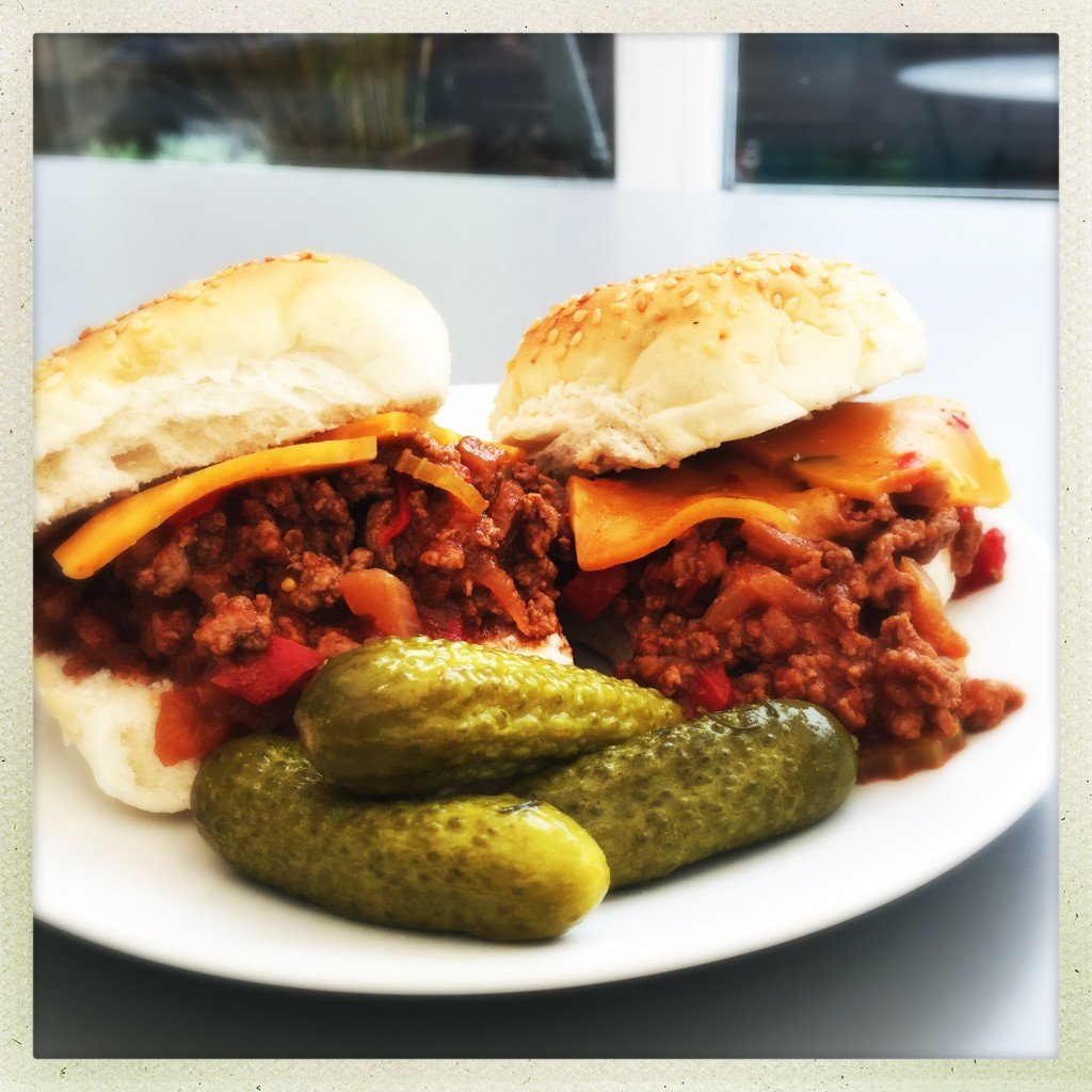 homemade sloppy joes made with ground beef served on rolls with cheese and gherkins.