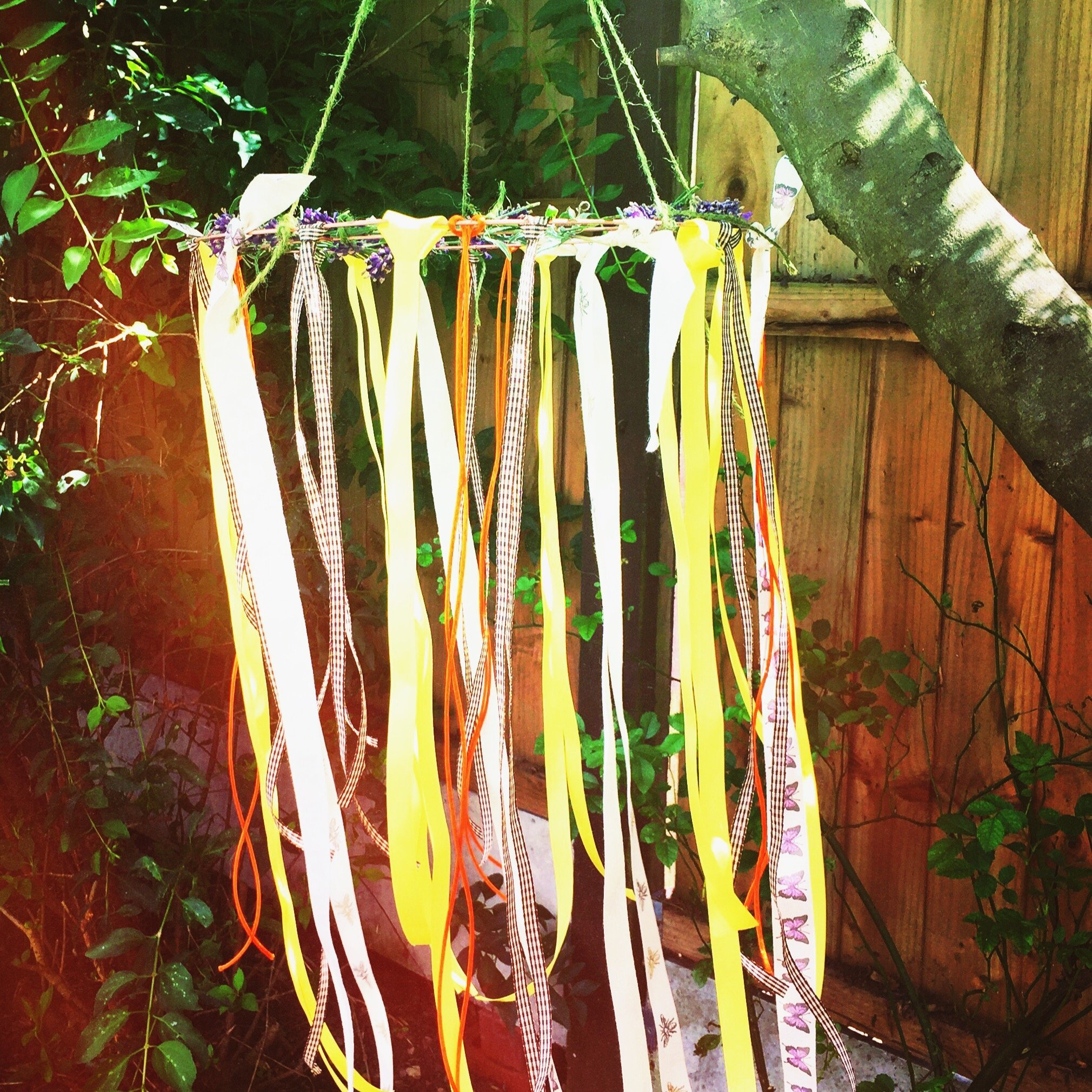 kids craft wind catcher with lavender and ribbons hanging from a tree in the garden