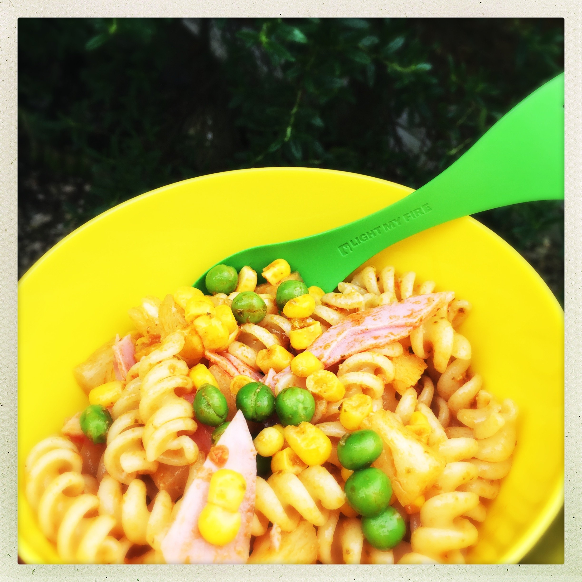 bright yellow plastic bowl filled with kids lunchbox pasta salad with ham, peas, pineapples, sweetcorn and a green plastic spork to eat it with