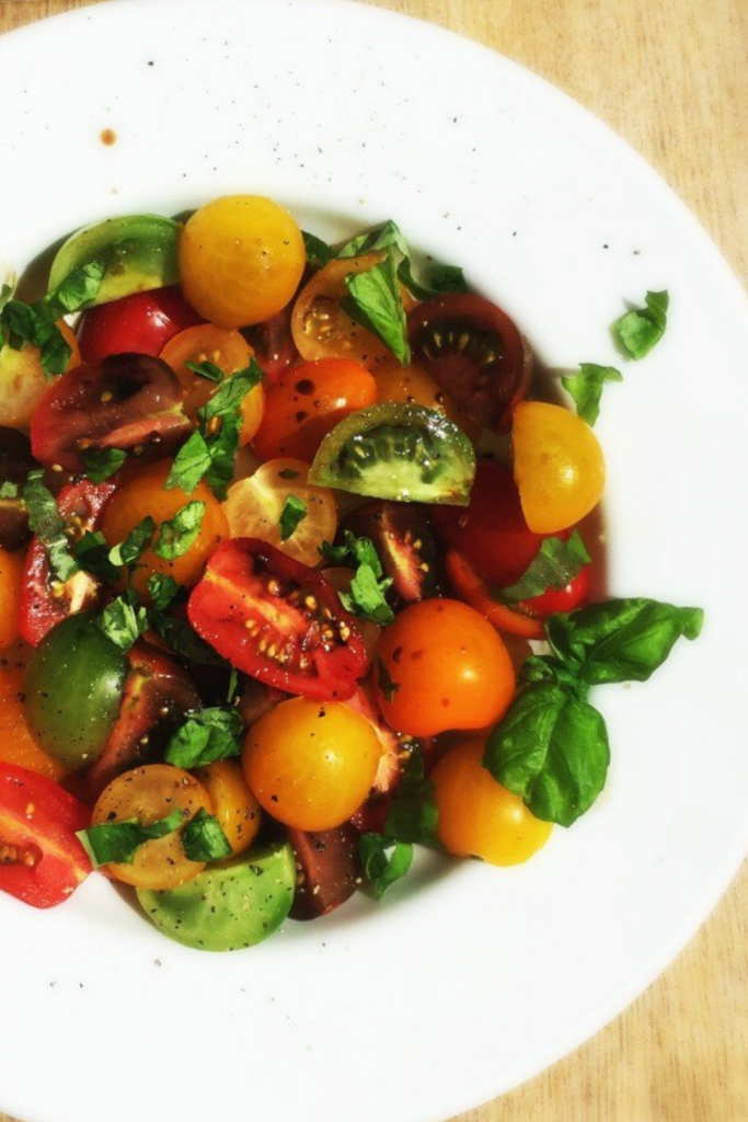 tomato salad made with heirloom tomatoes dressed with olive oil and basil