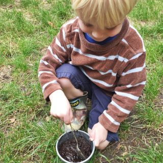 small blonde boy mixing up mud pies