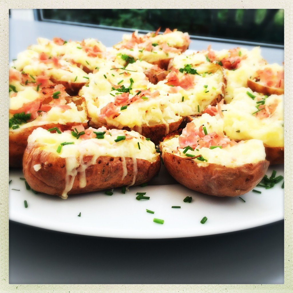 platter of loaded potato skins with ham and cheese scattered with chives.
