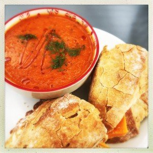 bowl of roast red pepper and tomato soup with cheese rolls
