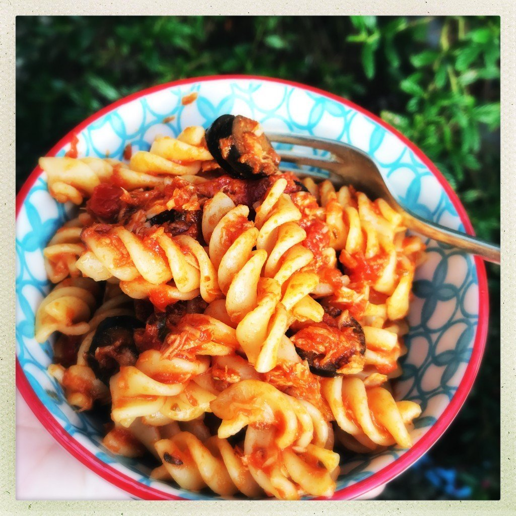 red and blue bowl filled with homemade tuna bolognese with fusilli pasta