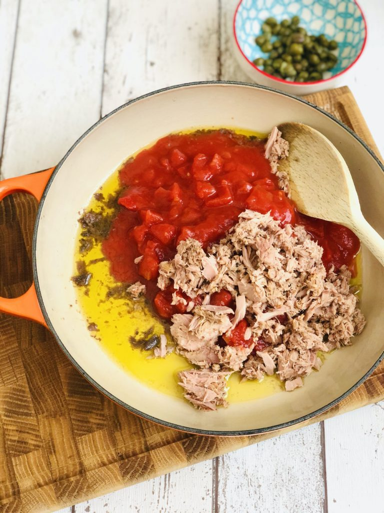 olive oil, anchovy fillets, canned tomatoes and canned tuna in a le creuset skillet pan