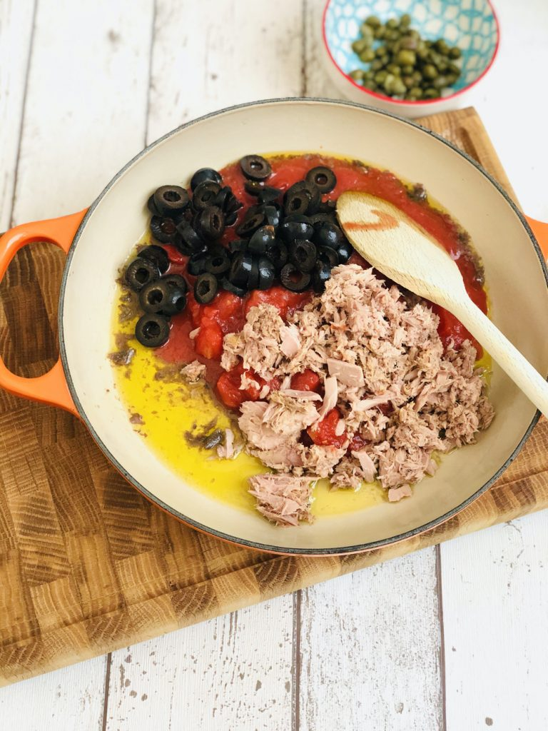 olive oil, anchovy fillets, canned tuna, canned tomatoes, sliced black olives in a le creuset skillet pan