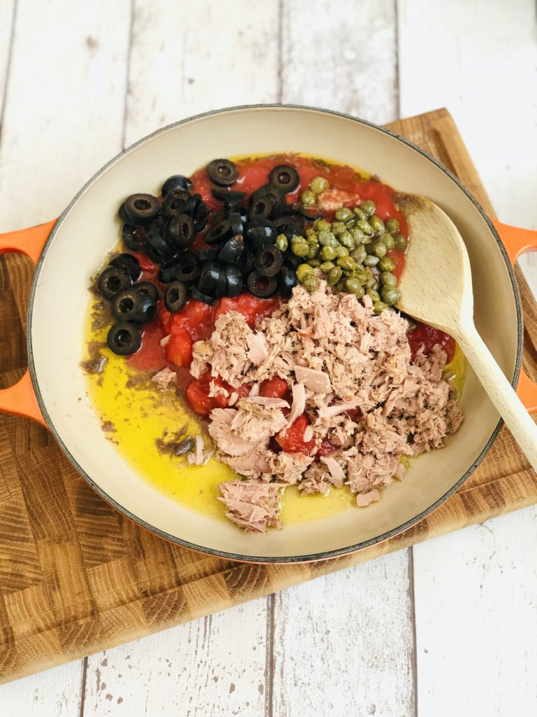 olive oil, anchovy fillets, canned tomatoes, canned tuna, sliced black olives and capers in a le creuset skillet pan