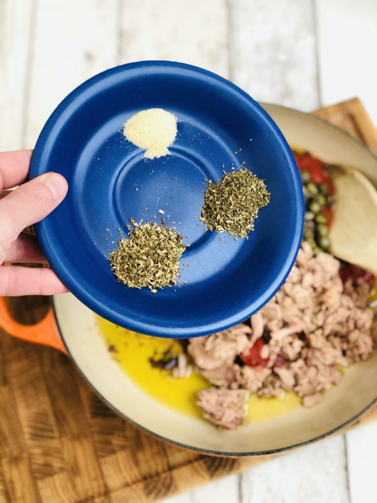garlic powder, dried basil and dried oregano on a blue saucer being tipped into a pan of tuna pasta bolognese