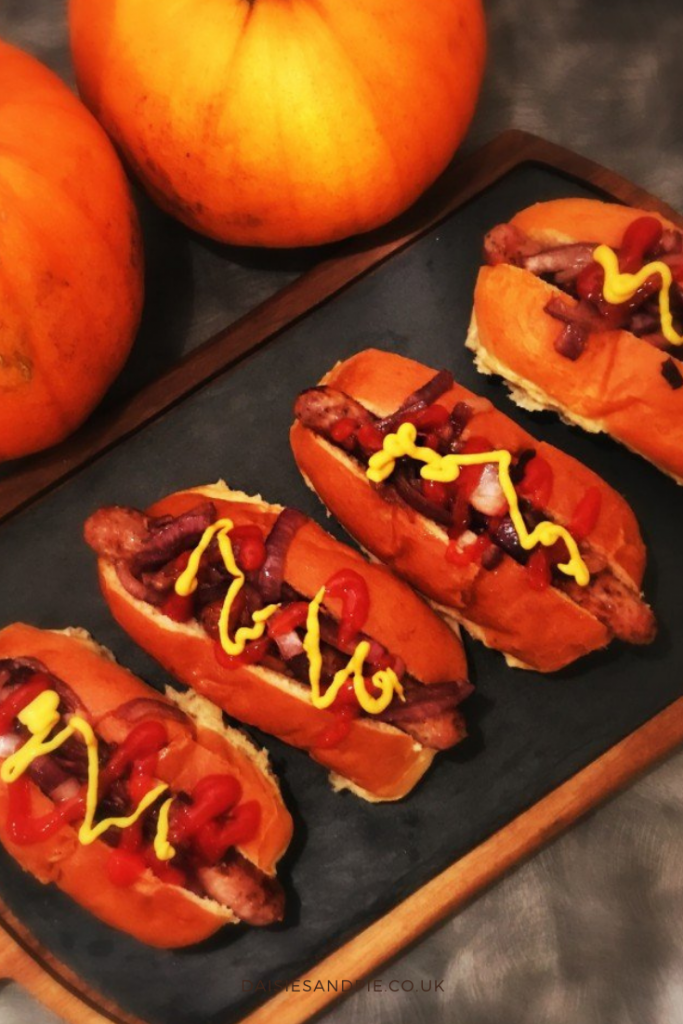 sticky bonfire night sausages served in brioche rolls with caramelised onions, ketchup and mustard - served on a black slate with pumpkins in the background