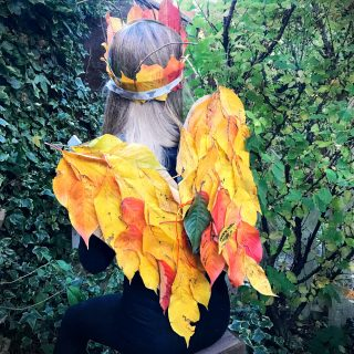 young girl dressed in black wearing fairy wings made from autumn leaves and a nature crown made from fallen autumn leaves