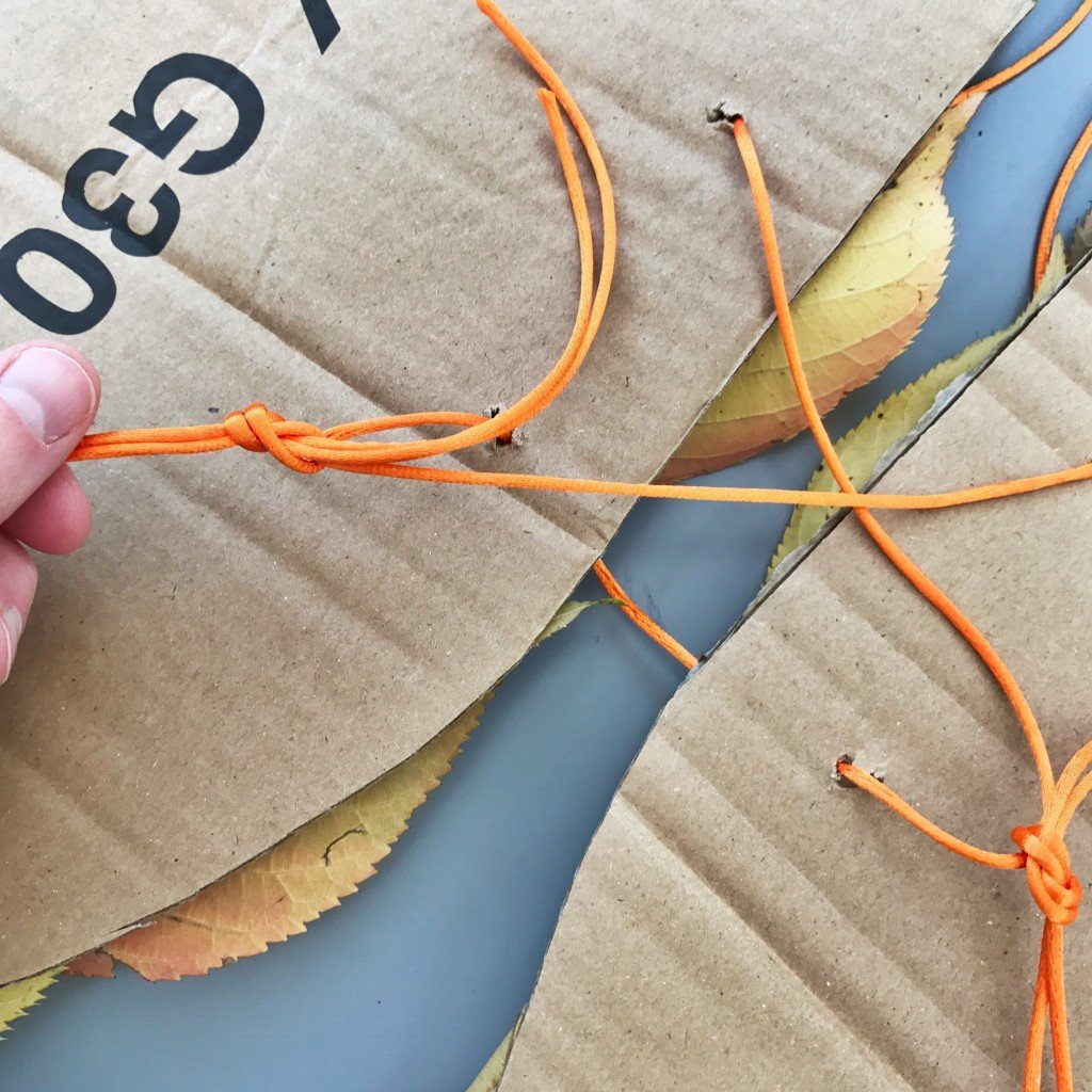 tying cardboard fairy wings together with string