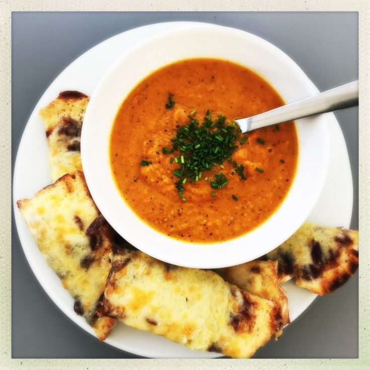 roasted sweet potato soup recipe served in white bowl scattered with herbs alongside grilled cheese sandwiches