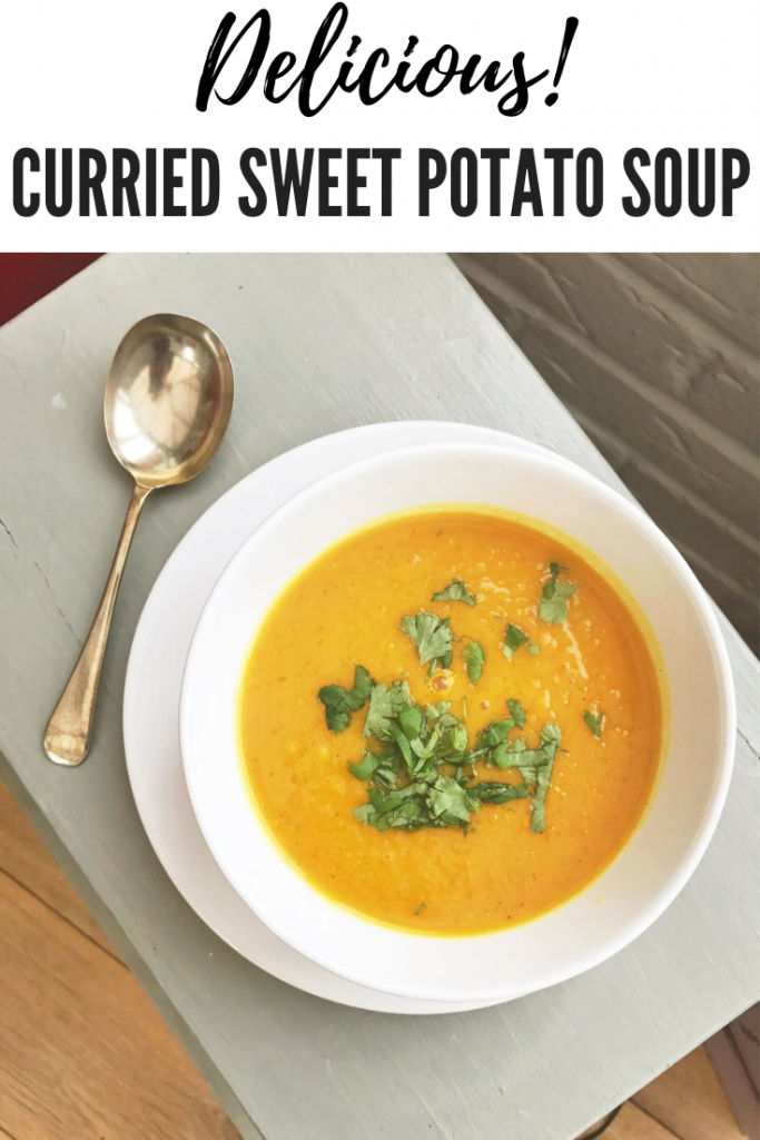 "bowlful of curried sweet potato soup with chopped corianders sprinkled on top. Text overlay reads ""delicious curried sweet potato soup"""