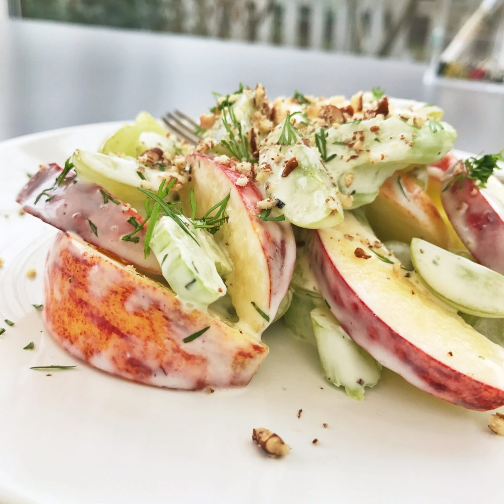 waldorf salad with apples, celery, walnuts and dill in a creamy dressing