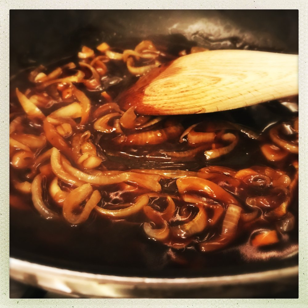 cheat onion gravy being stirred with a wooden spoon