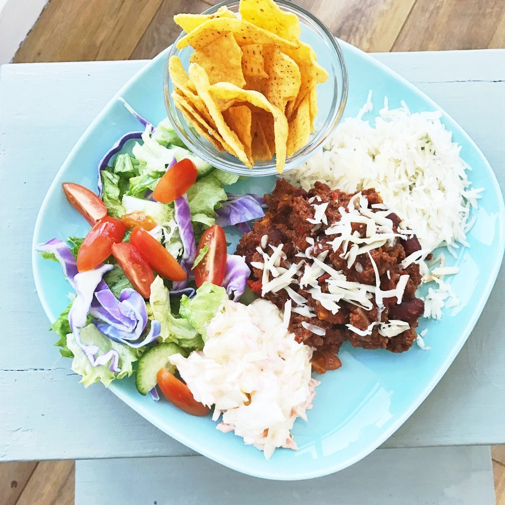 blue plate loaded with mild chilli con carne, nachos, big salad and pile of coleslaw