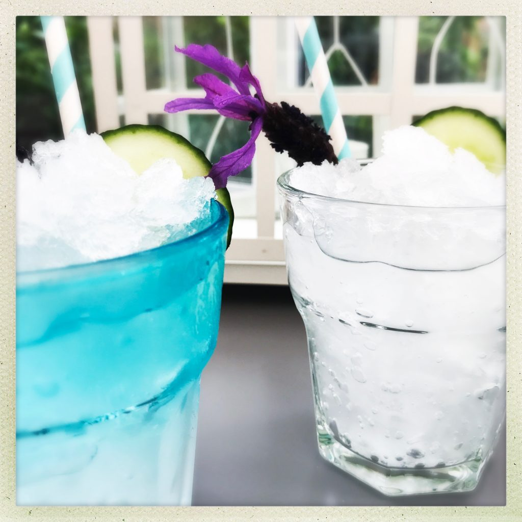 gin and tonic alcohol slushies in blue and clear glasses decorated with cucumber and lavender flowers