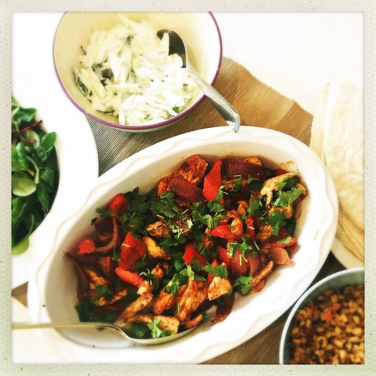 moroccan chicken with peppers and tomatoes, next to a bowl of mint raita, salad and couscous.