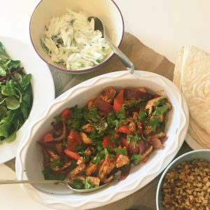 platter with moroccan chicken and vegetables in a serving bowl, alongside cucumber yogurt, salad leaves and quinoa