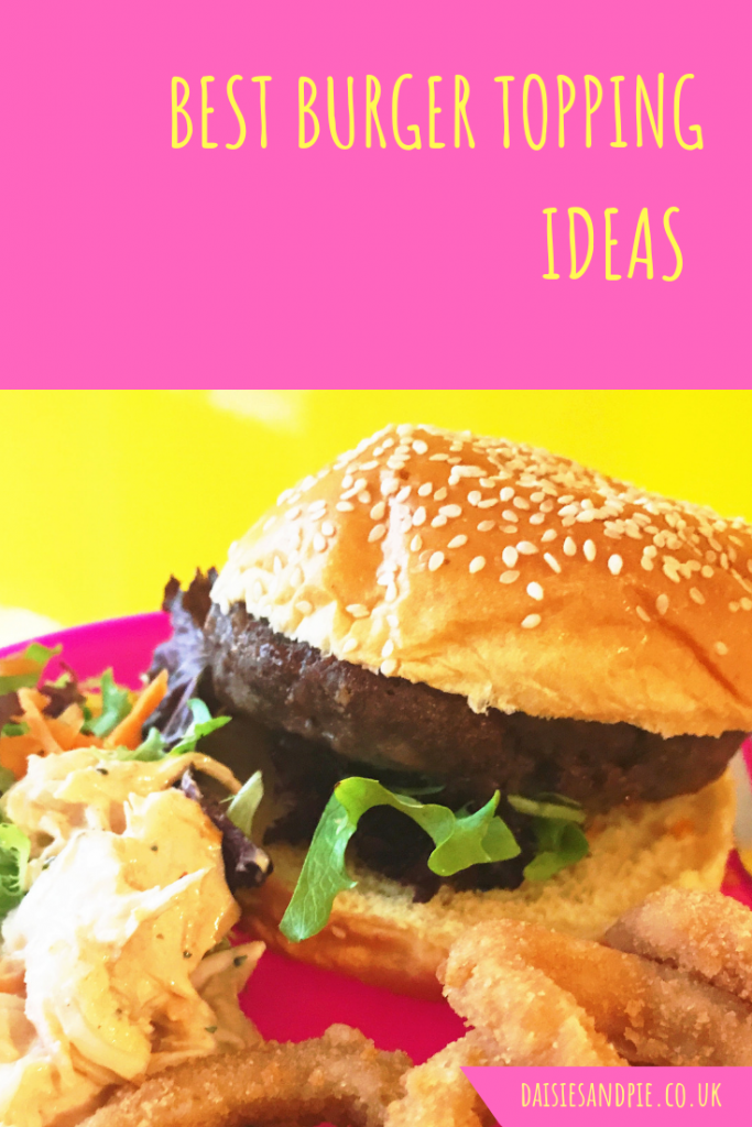 "burger with salad, cheese and onion rings. Text overlay saying ""best burger topping ideas"""