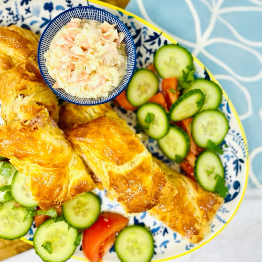 cheese and ham pie on a blue and white serving platter surrounded by salad and a bowl of coleslaw