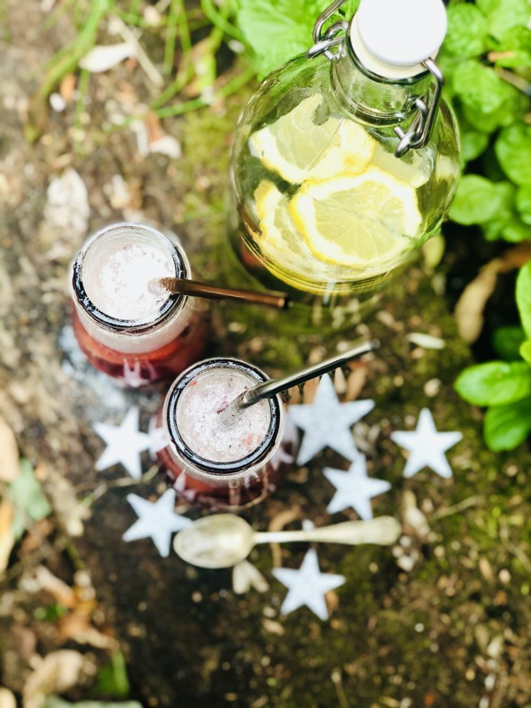 homemade fairy potion drinks with silver glitter bubbles on top - reusable stainless steel straws coming from the bottles