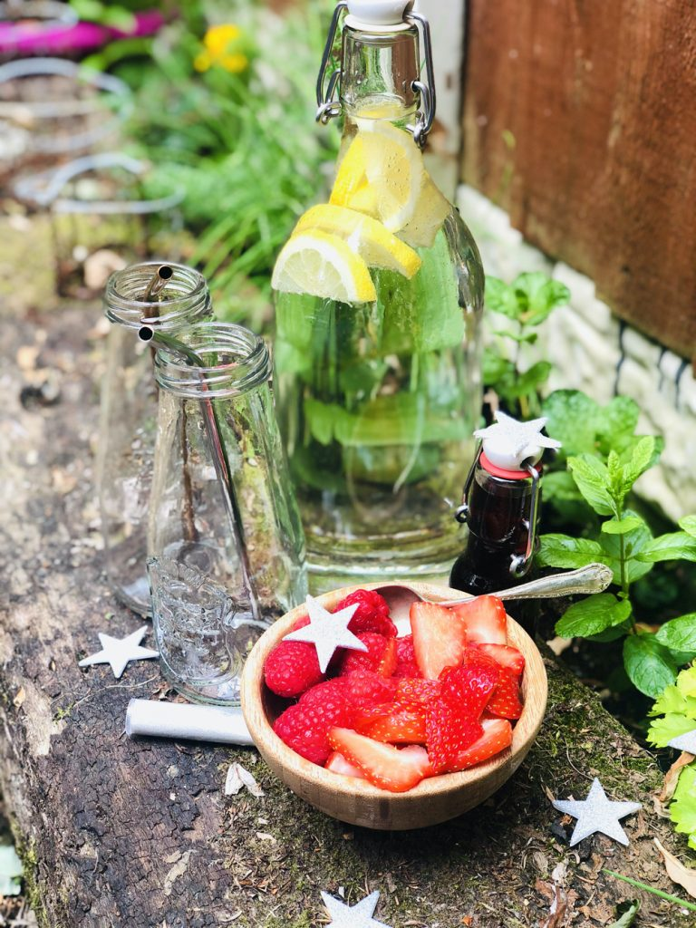all the ingredients for making fairy potion drinks set up in the garden on an old wooden sleeper surrounded by growing herbs - small wooden bowl of raspberries and strawberries, two glass bottles with stainless steel reusable straws, a bottle of lemonade with lemons in it and a small bottle of red berry cordial alongside a tube of edible glitter and a vintage teaspoon