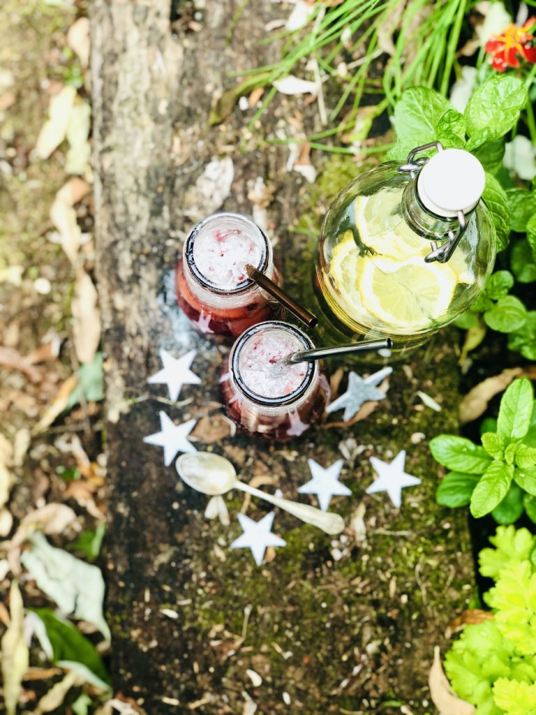 fairy potion drinks with edible glitter, strawberries, raspberries and red berry cordial, surrounded by silver stars on an old wooden sleeper in the garden