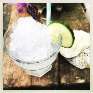 Glass of gin and tonic slushy garnished with cucumber slice, fresh lavender flower and stripy blue and white paper straw . Slushy is on weather beaten old railway sleeper with seashells by the glass