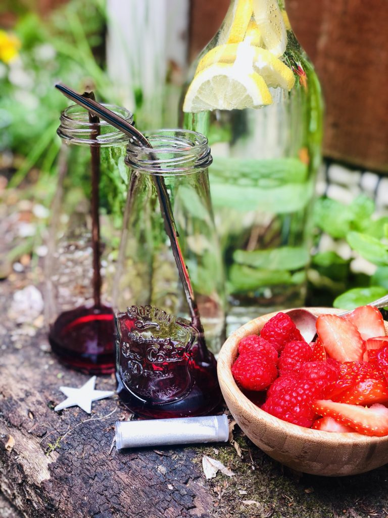 red berry cordial poured into the bottom of two drinking bottles with reusable stainless steel straws in them a bowl of strawberries and raspberries to the side